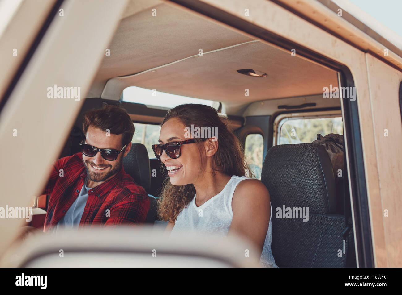 Young Couple Sitting In Their Car During Roadtrip. Young Man And Woman  Wearing Sunglasses Sitting