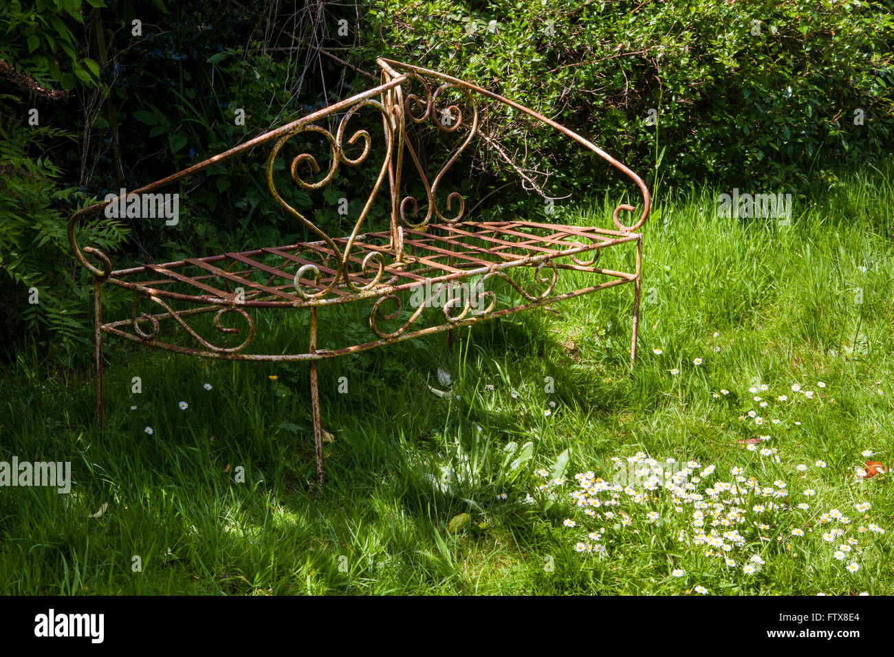 Old garden furniture made from iron etc sitting in an overgrown garden. Old garden furniture made from iron etc sitting in an overgrown