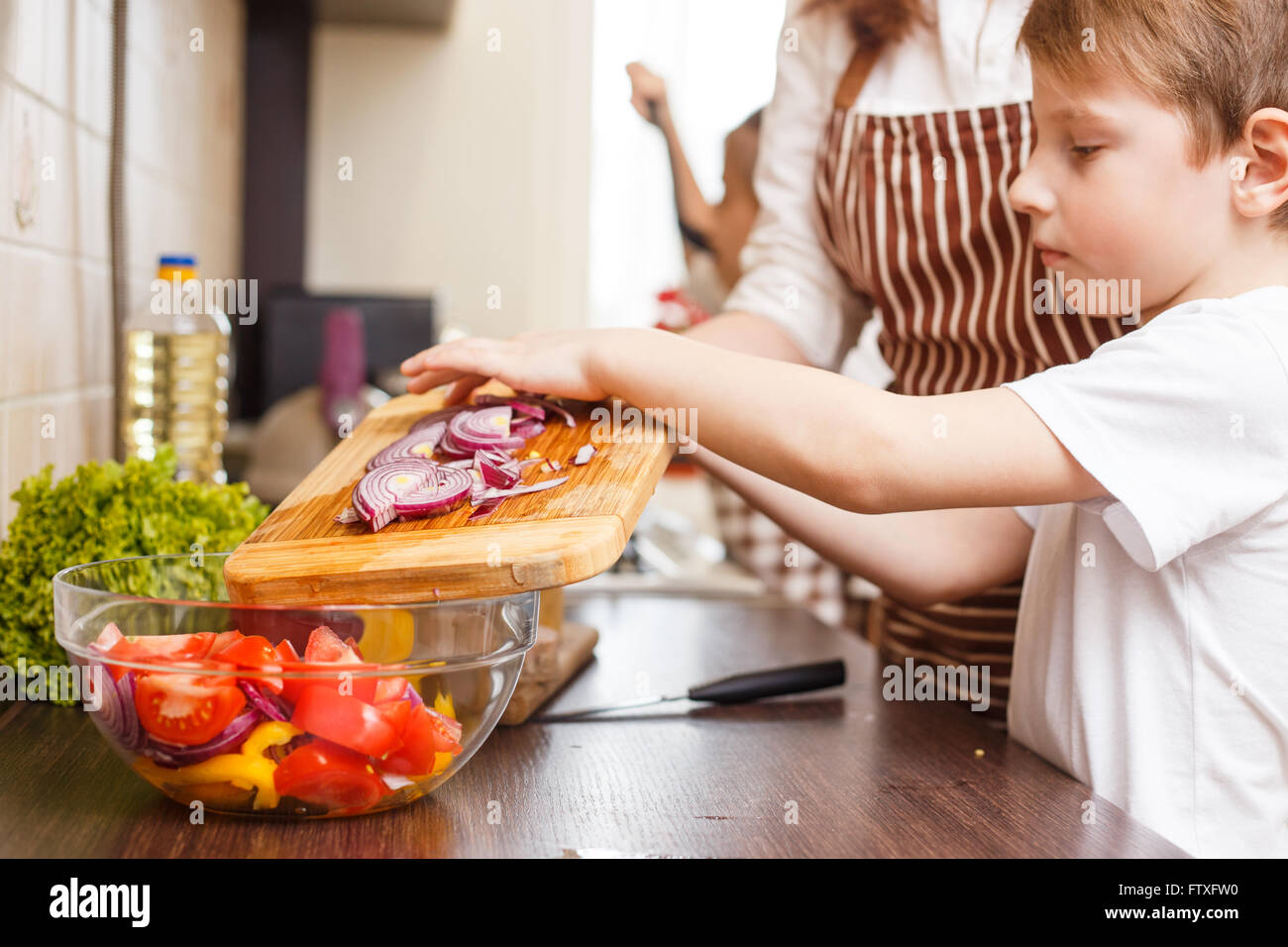 Family cooking kitchen - Family Cooking Background Small Boy Help His Mother With Cutting Onion For Salad In The Kitchen