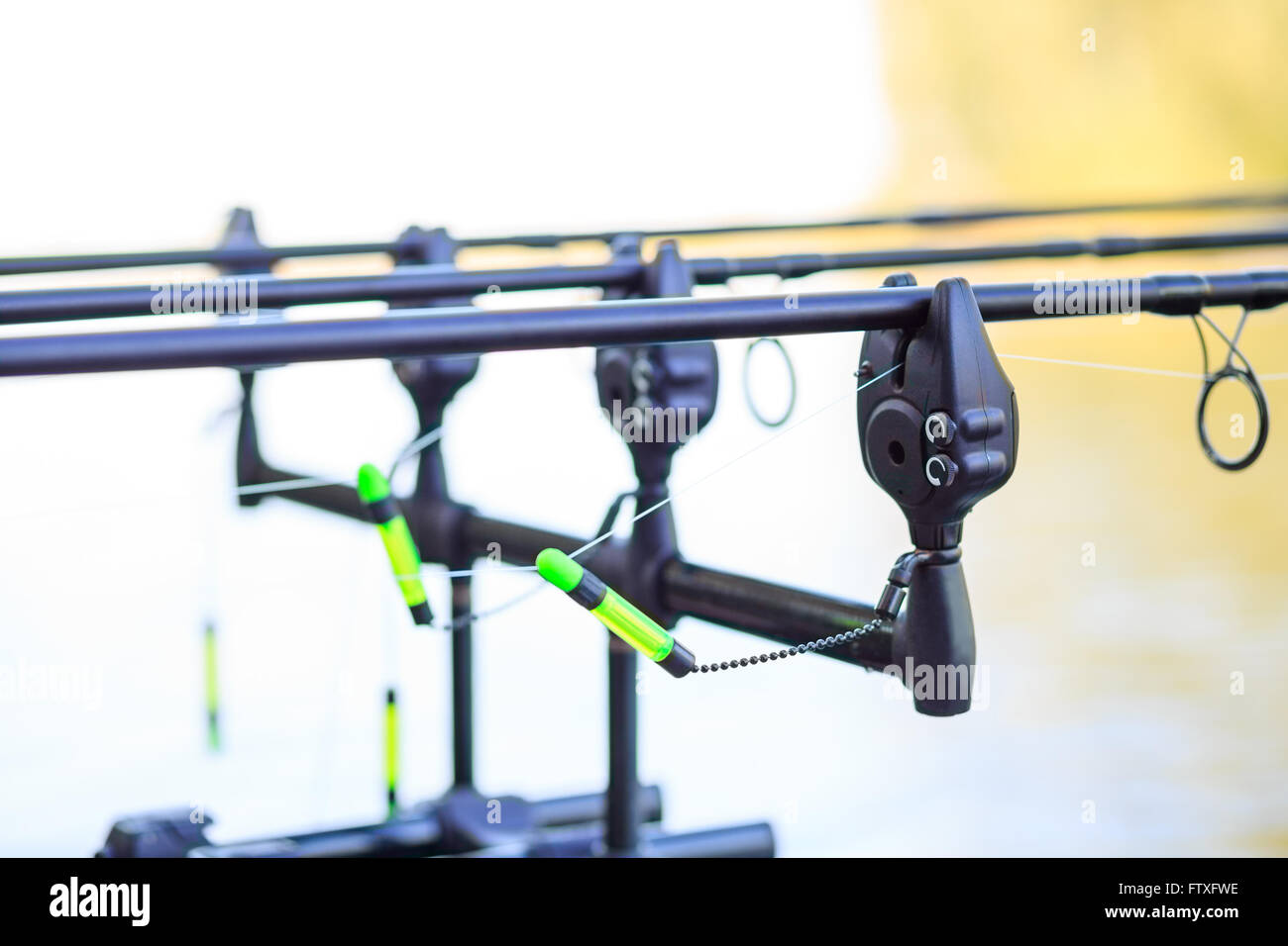 Carp fishing rods set up on holder with bite alarms and ...