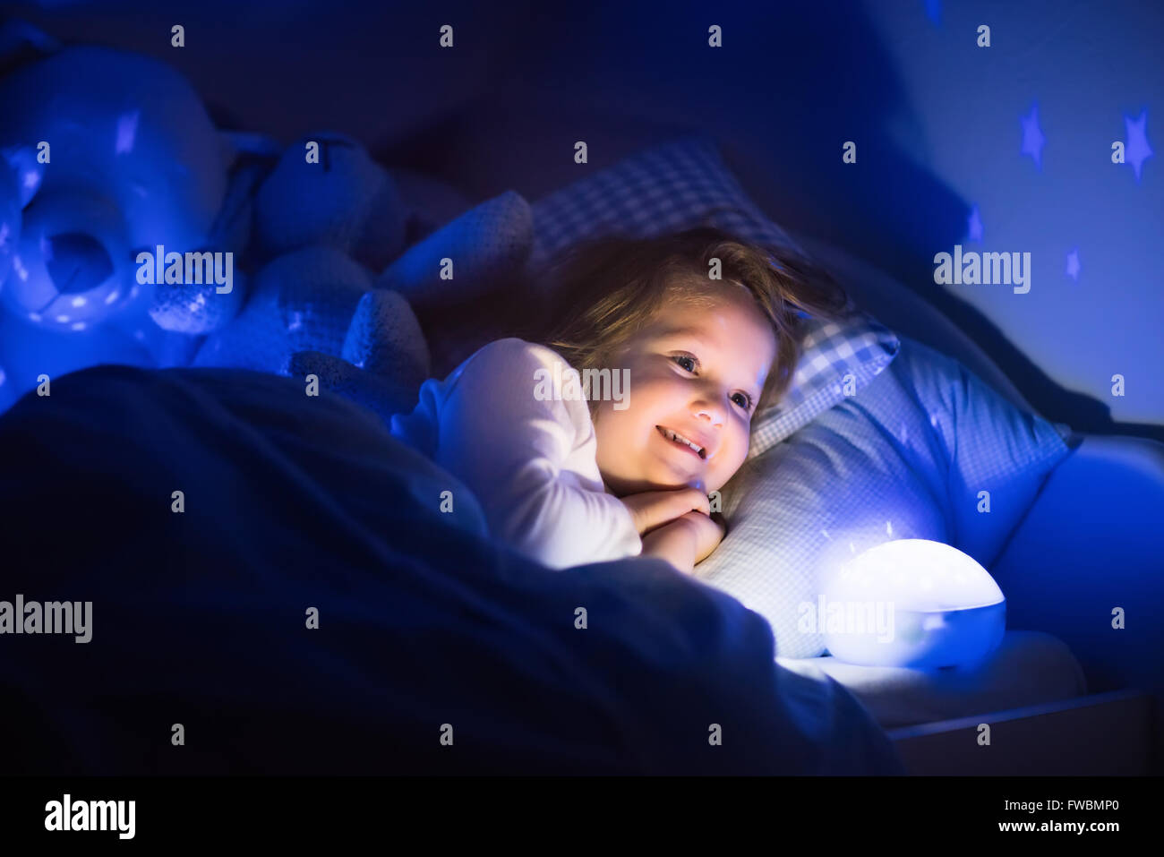 Dark Bedroom At Night little girl reading a book in bed. dark bedroom with night light