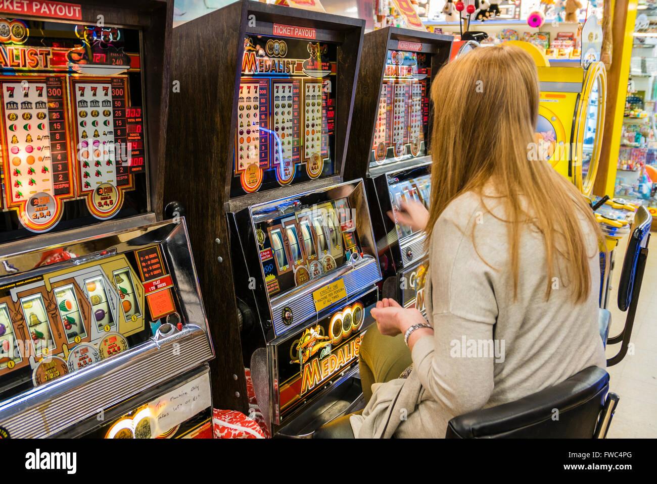 A woman plays a 2p slot machine in a funfair at a British ...