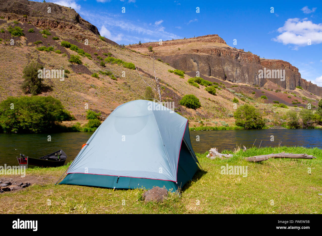 A rustic tent c&site on the Deschutes River in Oregon shows a tent setup next to a boat and the river. This is form a float ca & A rustic tent campsite on the Deschutes River in Oregon shows a ...