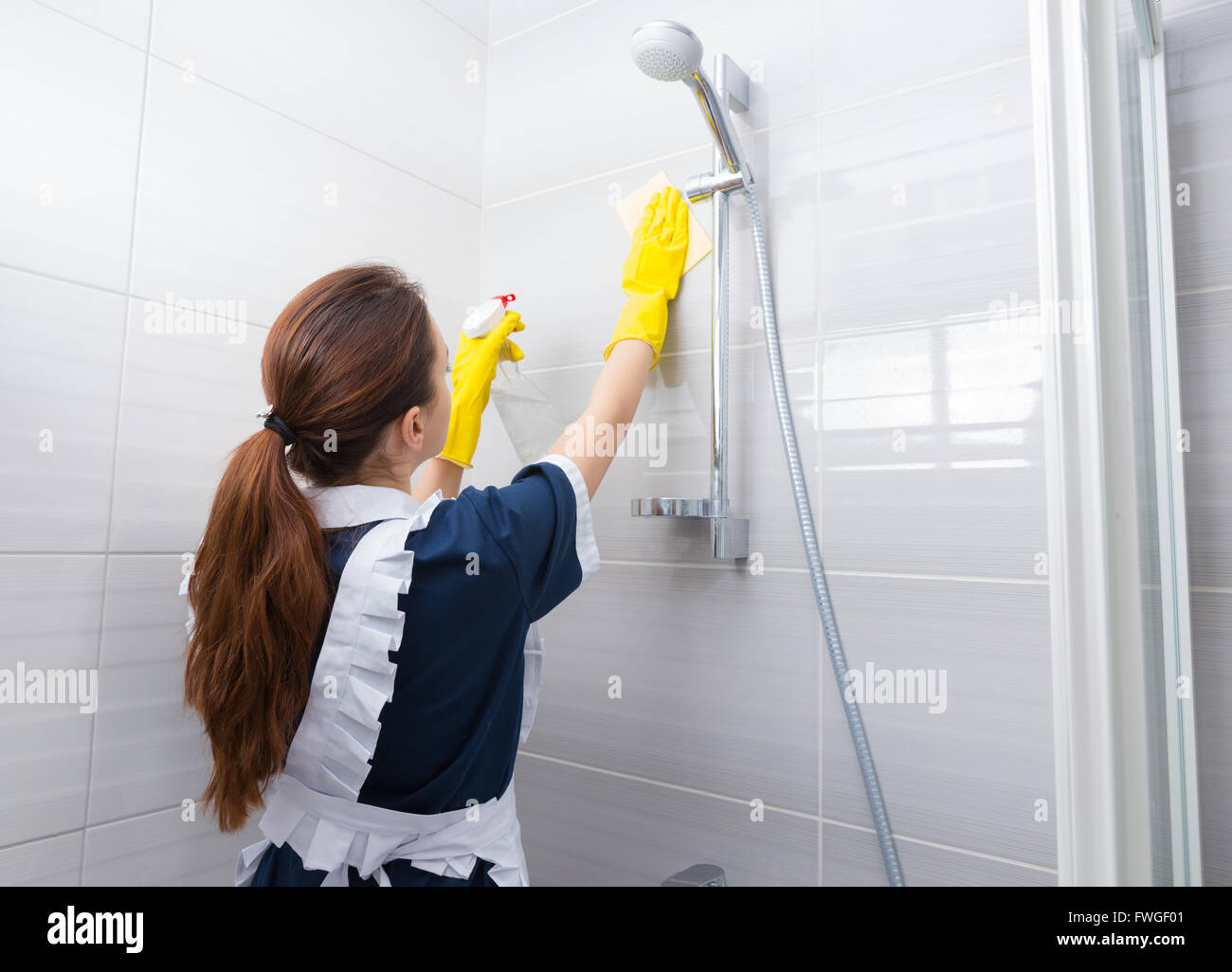 housekeeper cleaning the shower head in the bathroom reaching up to stock photo royalty free. Black Bedroom Furniture Sets. Home Design Ideas