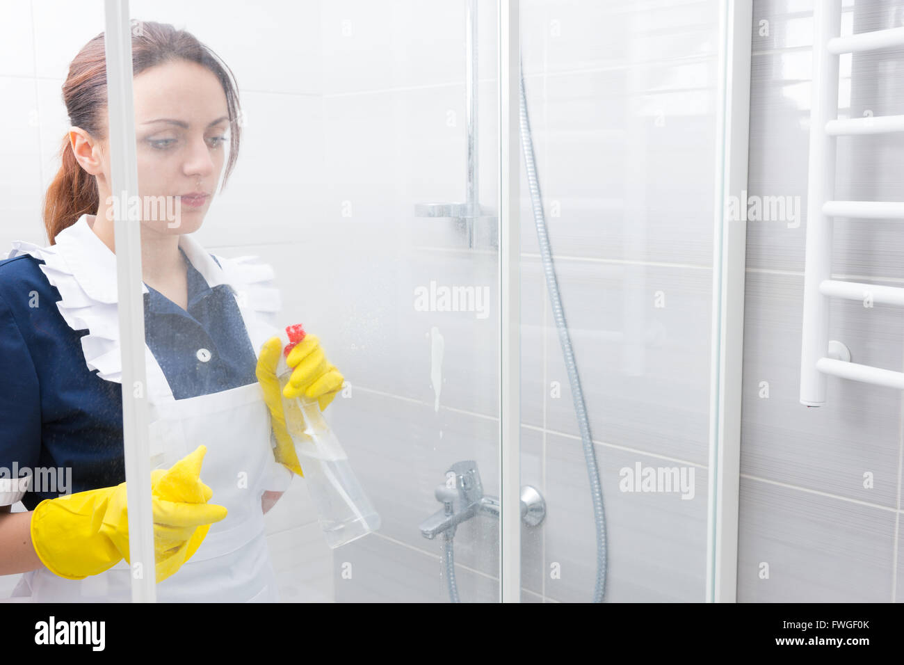 White apron maid - Maid Or Housekeeper Wearing A White Apron And Uniform Cleaning A White Bathroom Spraying The Glass