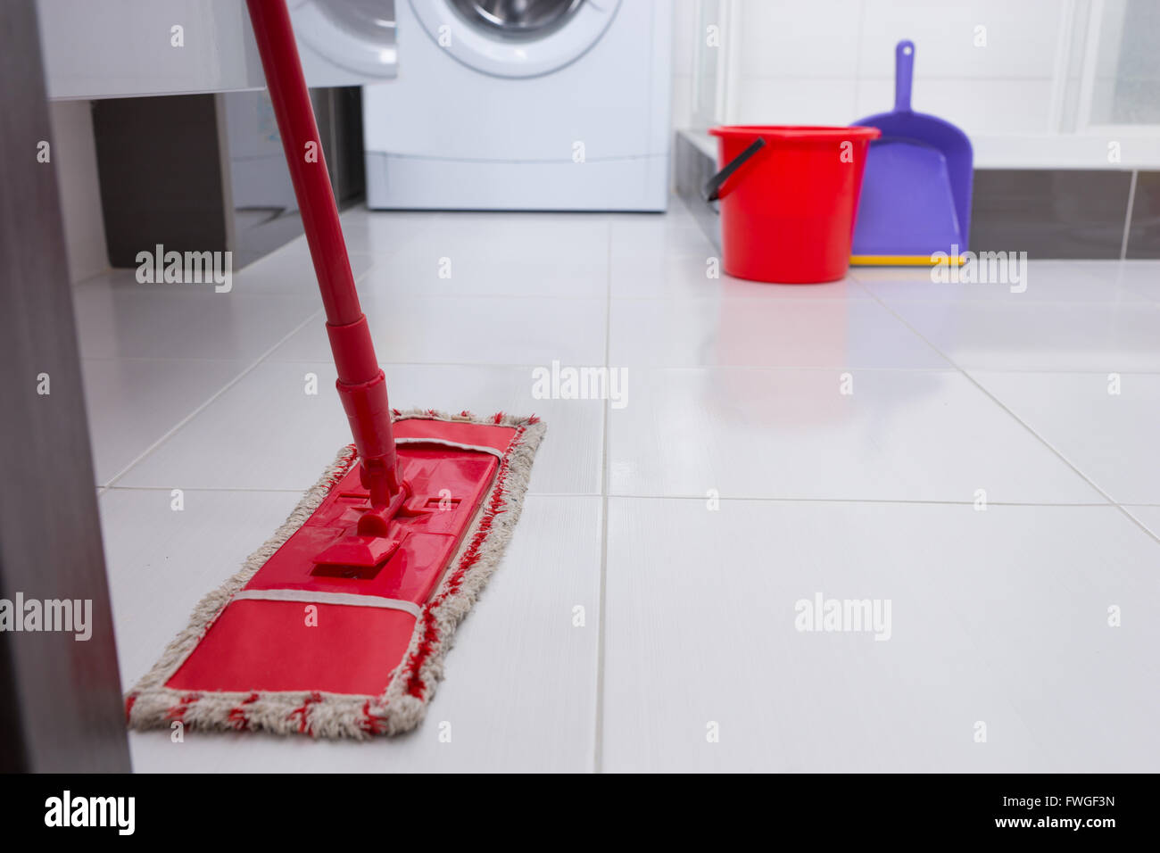 Colorful red mop on a white tiled floor in a bathroom or laundry colorful red mop on a white tiled floor in a bathroom or laundry with a washing machine visible behind low angle close up view dailygadgetfo Choice Image