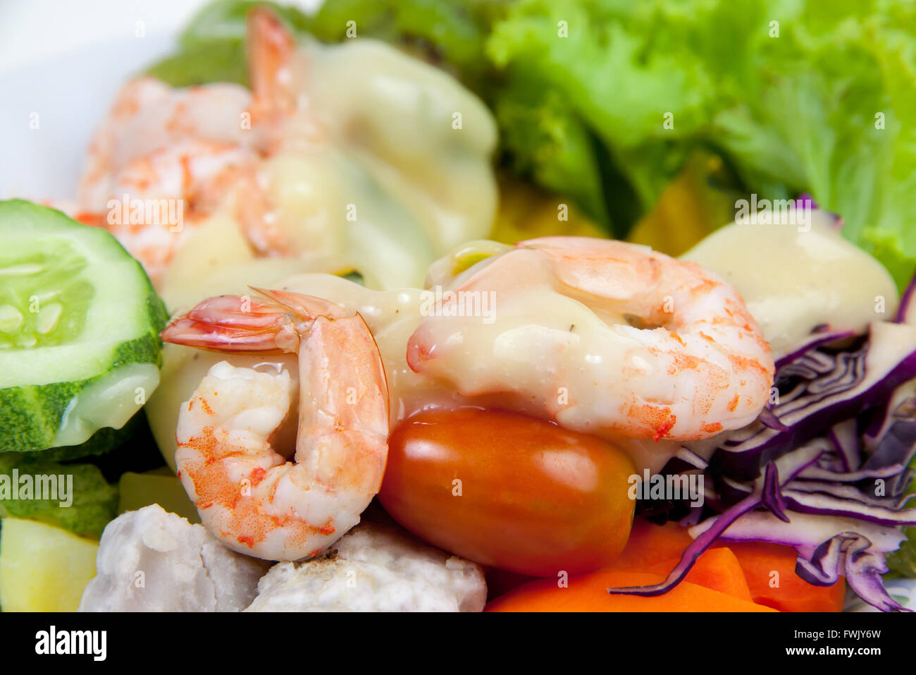 closeup boiled shrimp and vegetables and fruits put salad dressing