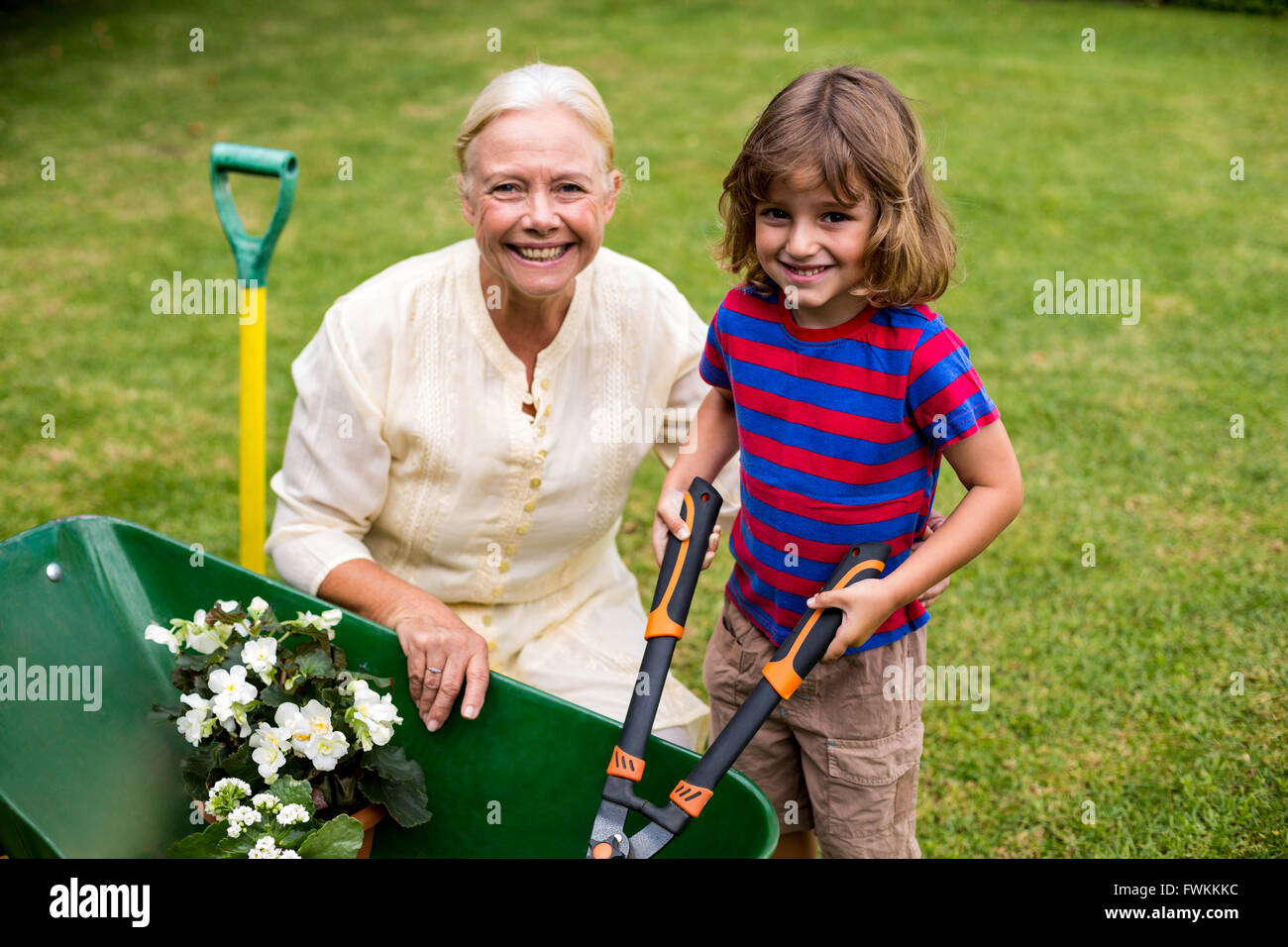 granny boy Boy with granny holding scissors over wheelbarrow at yard