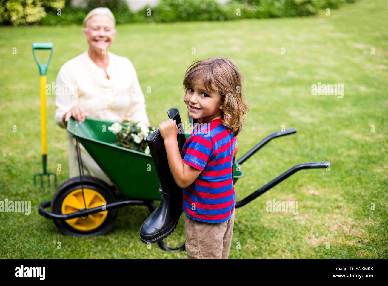 granny boy Boy holding wellington boots besides granny in yard Stock Photo