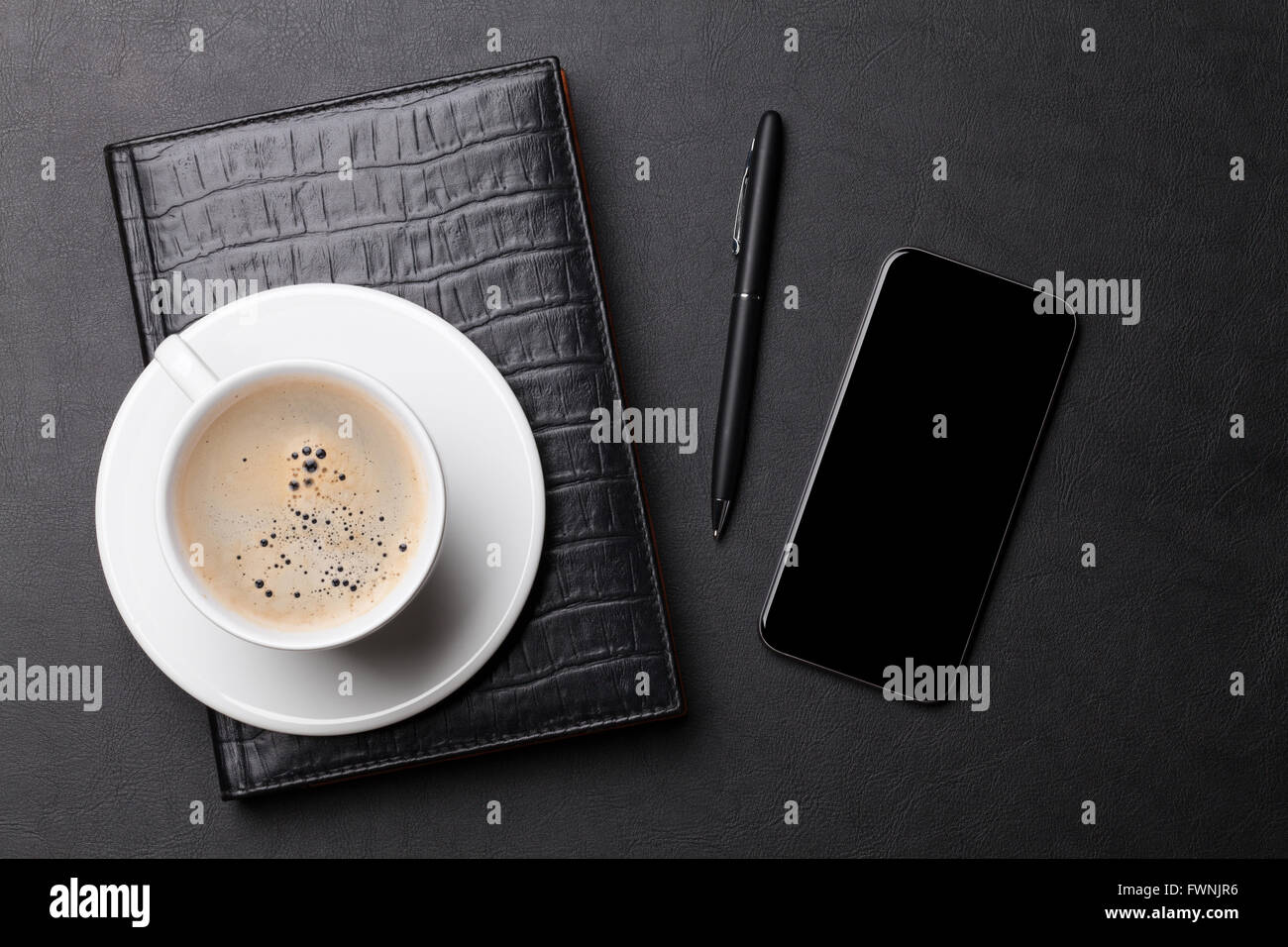 Office leather desk table with coffee cup notepad smartphone and