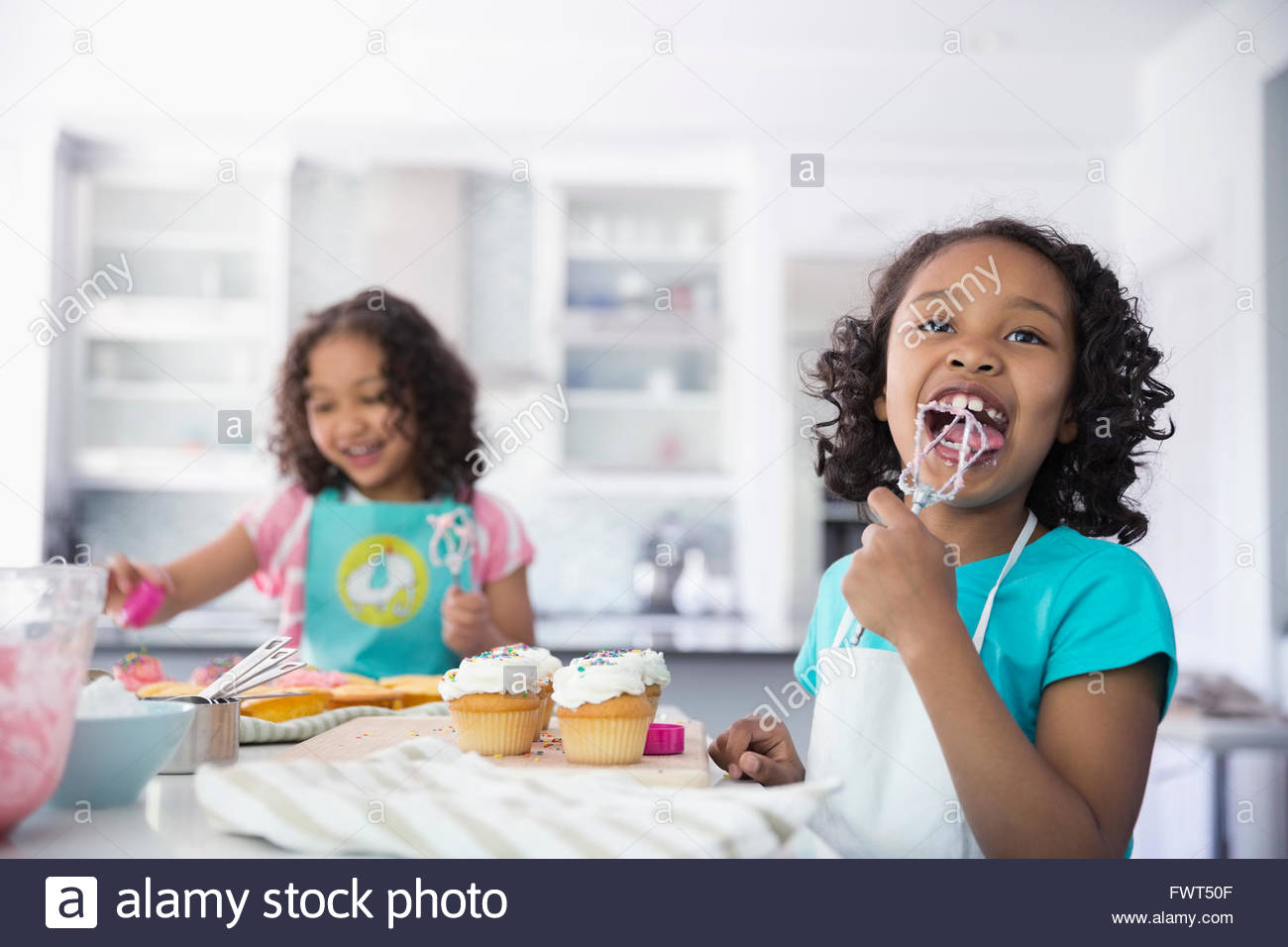 little girl licking icing off whisk while decorating cupcakes - Woman Decorating Cupcakes