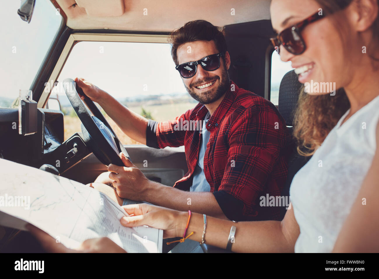 Genial Young Couple Sitting Inside Their Car With Map. Smiling Young Man And Woman  Sitting Together And Looking At The Map For Directio