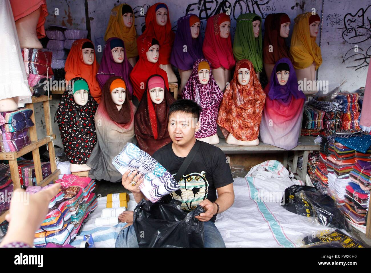 Jakarta, Indonesia. 01st Mar, 2016. A clothing vendor takes an ...