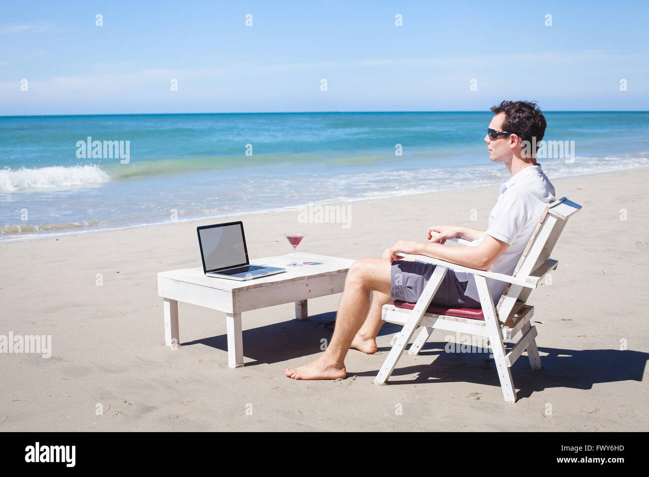 telecommuting businessman relaxing on the beach laptop and stock photo telecommuting businessman relaxing on the beach laptop and cocktail lancer workplace dream job