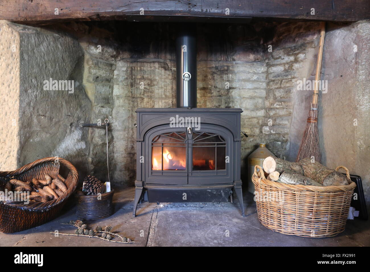 Wood Burning Stove In Inglenook Fireplace Stock Photo