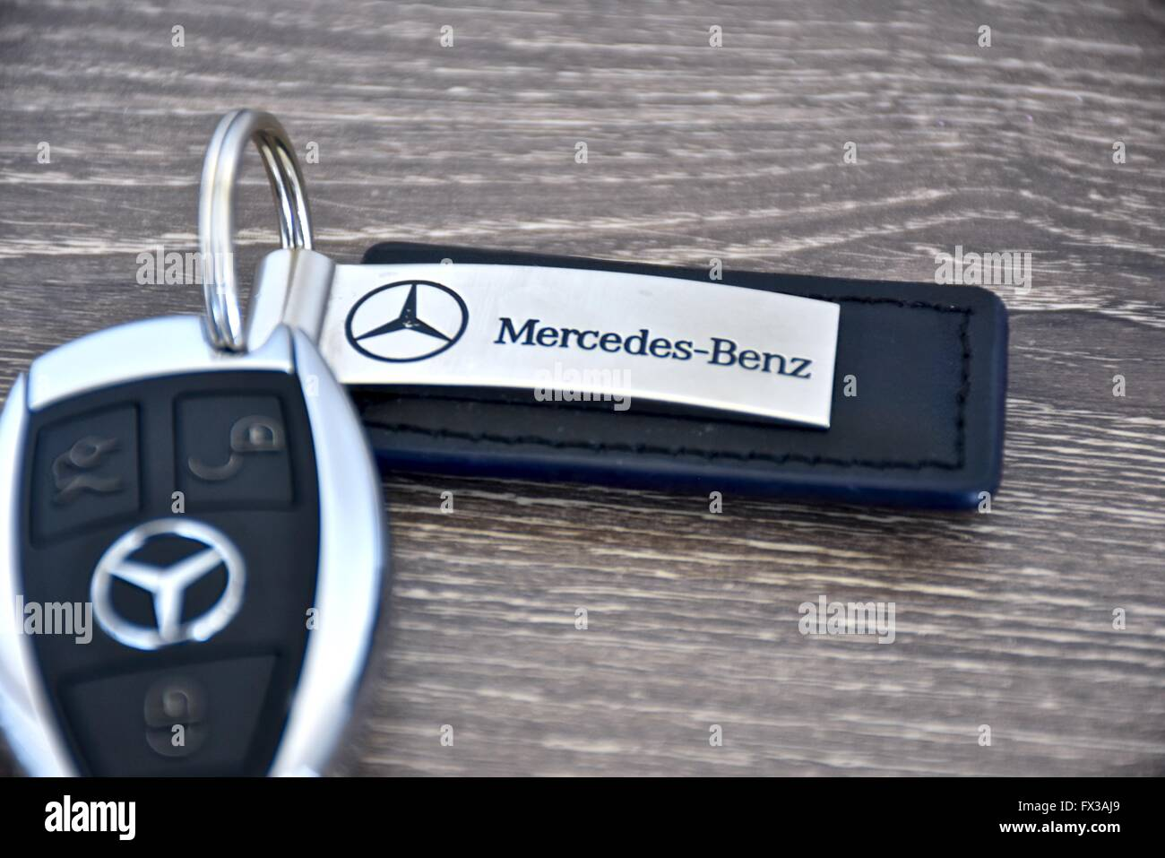 A mercedes benz key fob laying on a wood surface stock for Mercedes benz key fob