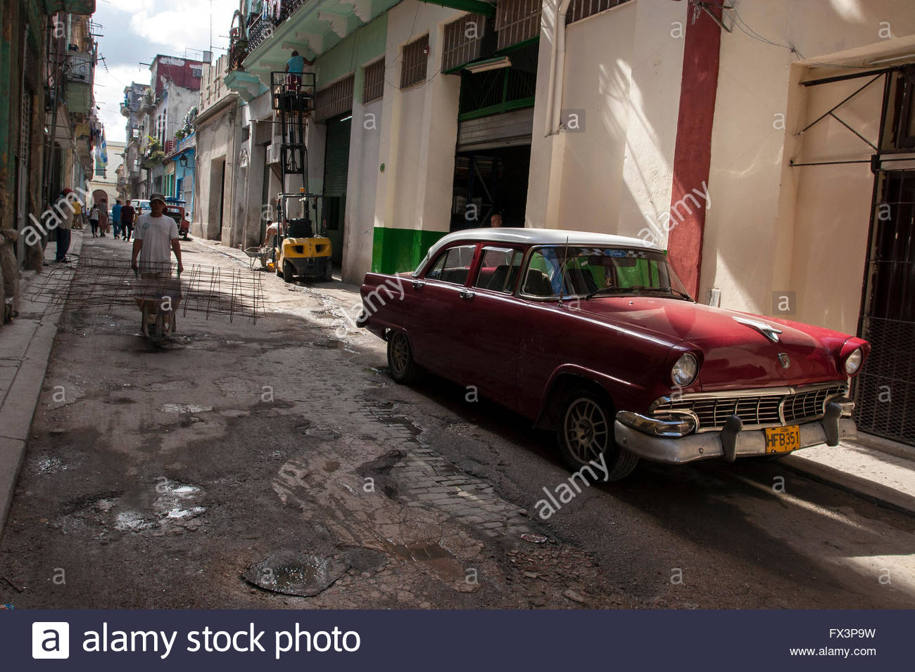 Vintage Ford Car on street in Havana, man with construction ...