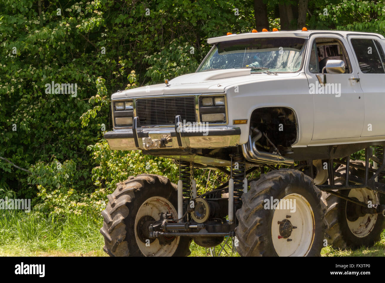 a white pickup truck modified as a monster truck stock photo