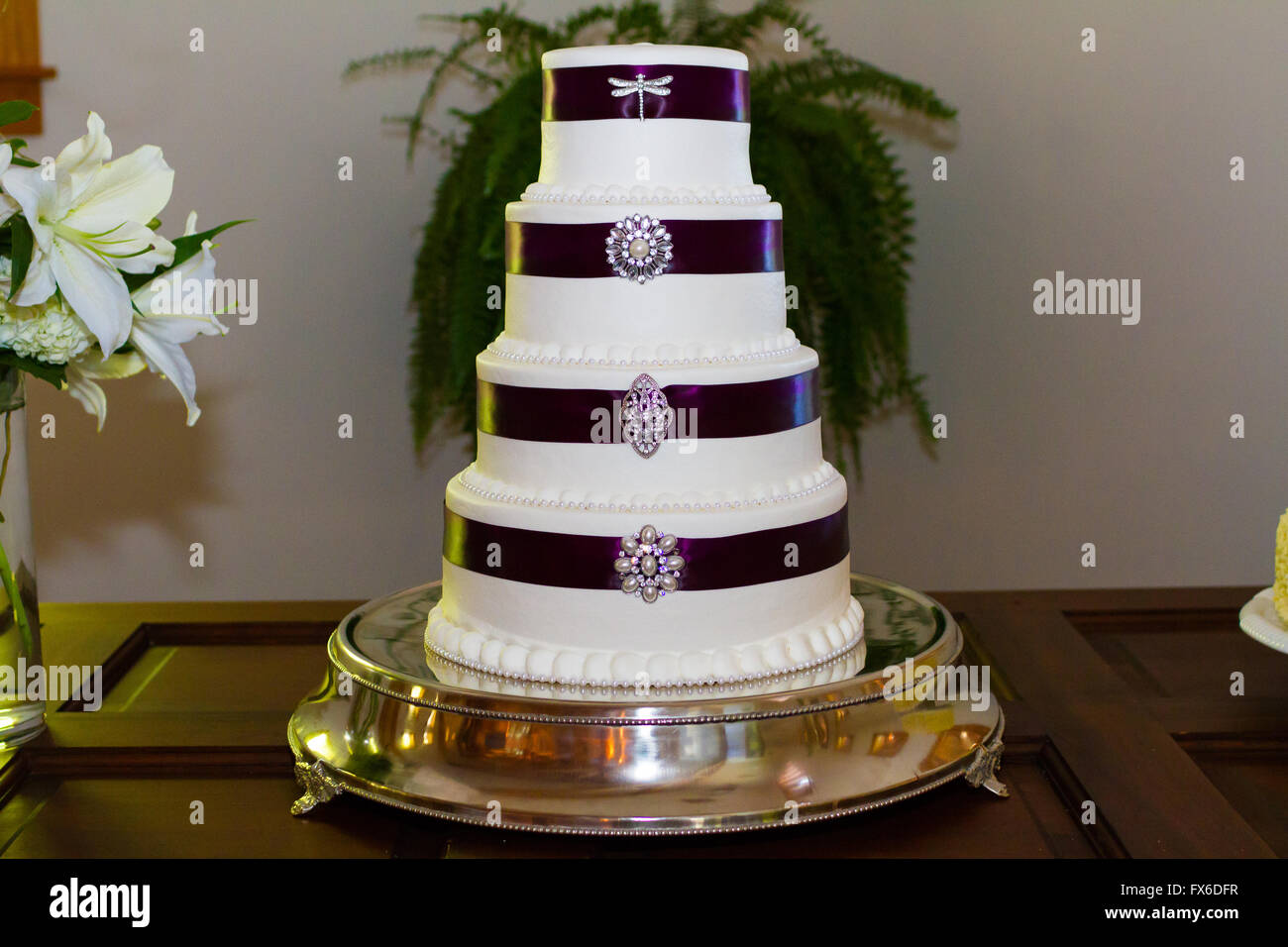 Tall white wedding cake wrapped in purple ribbon with brooches ...