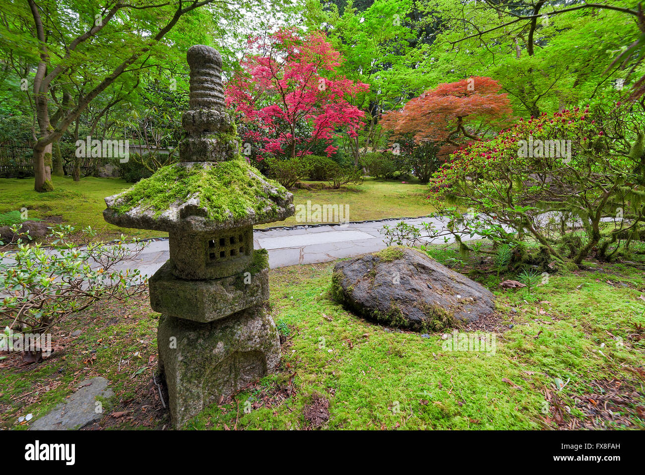 Old stone lantern in japanese garden with trees and shrubs for Japanese landscape lanterns