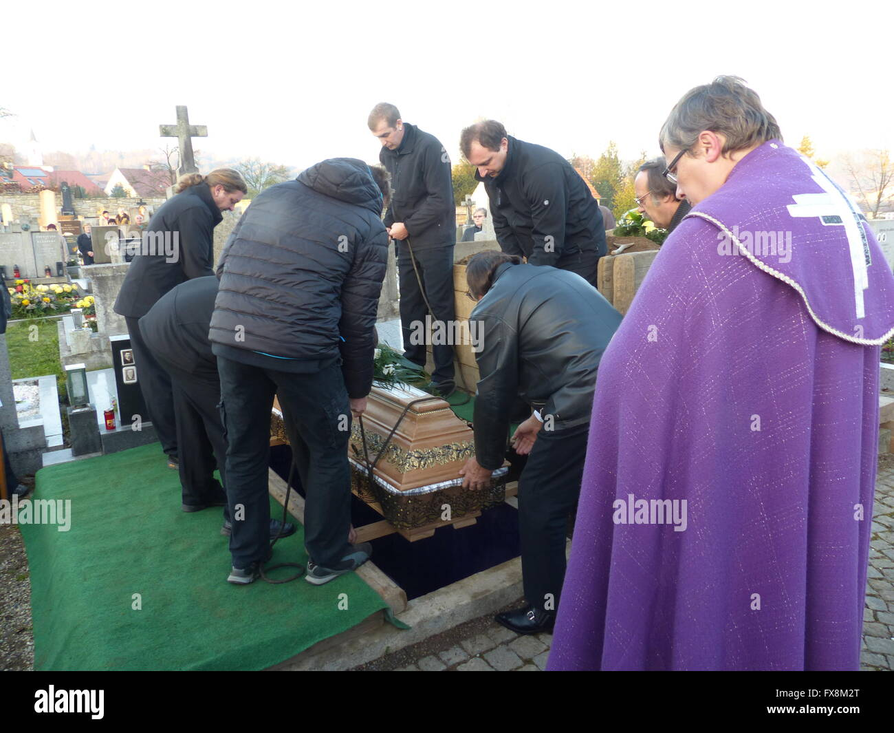 Lowering casket into grave at country funeral stock image