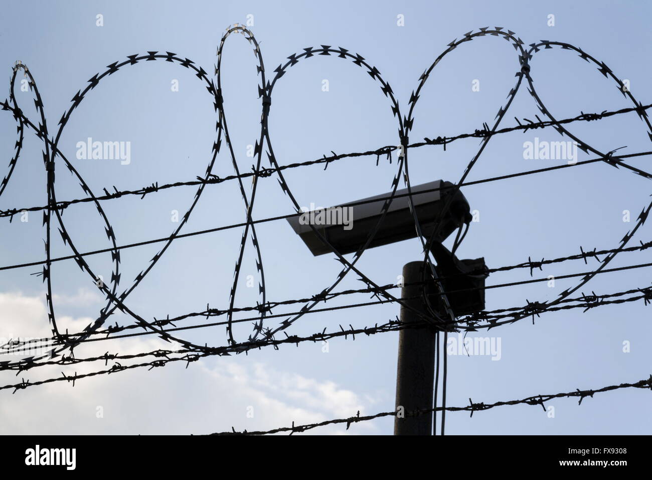 Security camera behind barbed wire fence stretched around