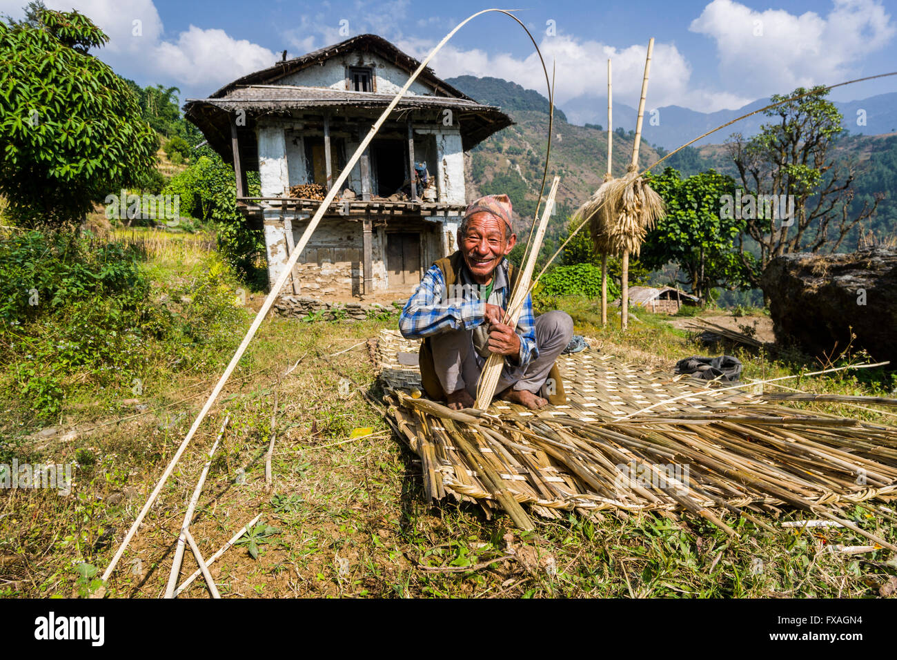Man building a woven bamboo fence to be used as a wall in front of man building a woven bamboo fence to be used as a wall in front of his farmers house bung solo khumbu nepal baanklon Image collections