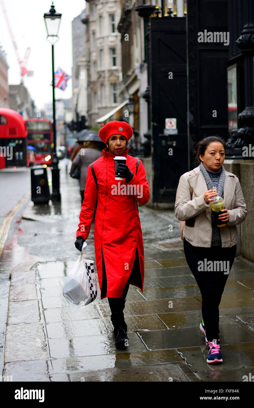woman in red coat and hat with coffee walking in the rain Stock ...