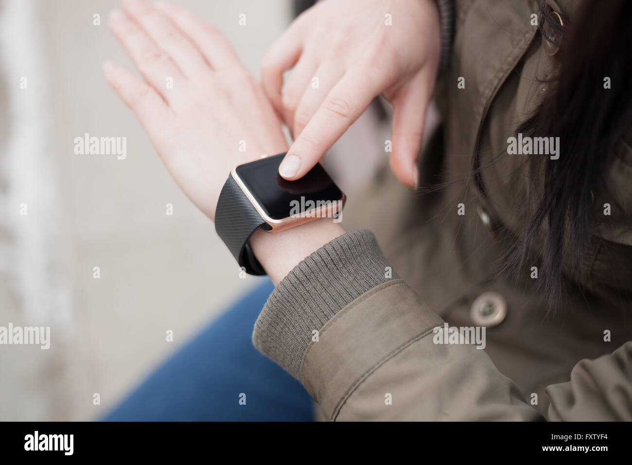 Hands of a girl using her trendy smart wrist watch. This new ...