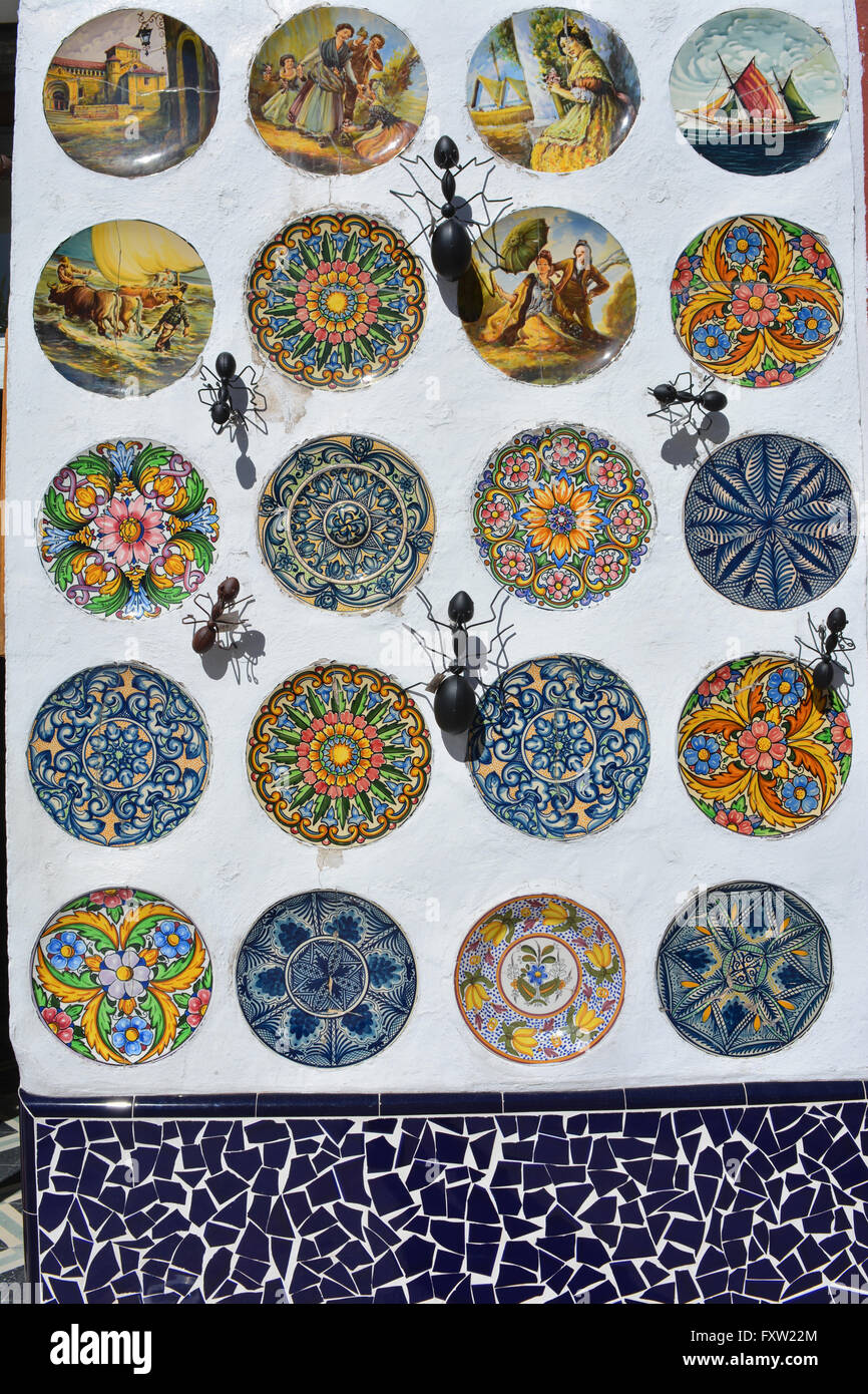 Display of hand-painted ceramic plates and metal ants decorating the wall of a souvenir shop Gata de Gorgos Valencia Spain & Display of hand-painted ceramic plates and metal ants decorating the ...