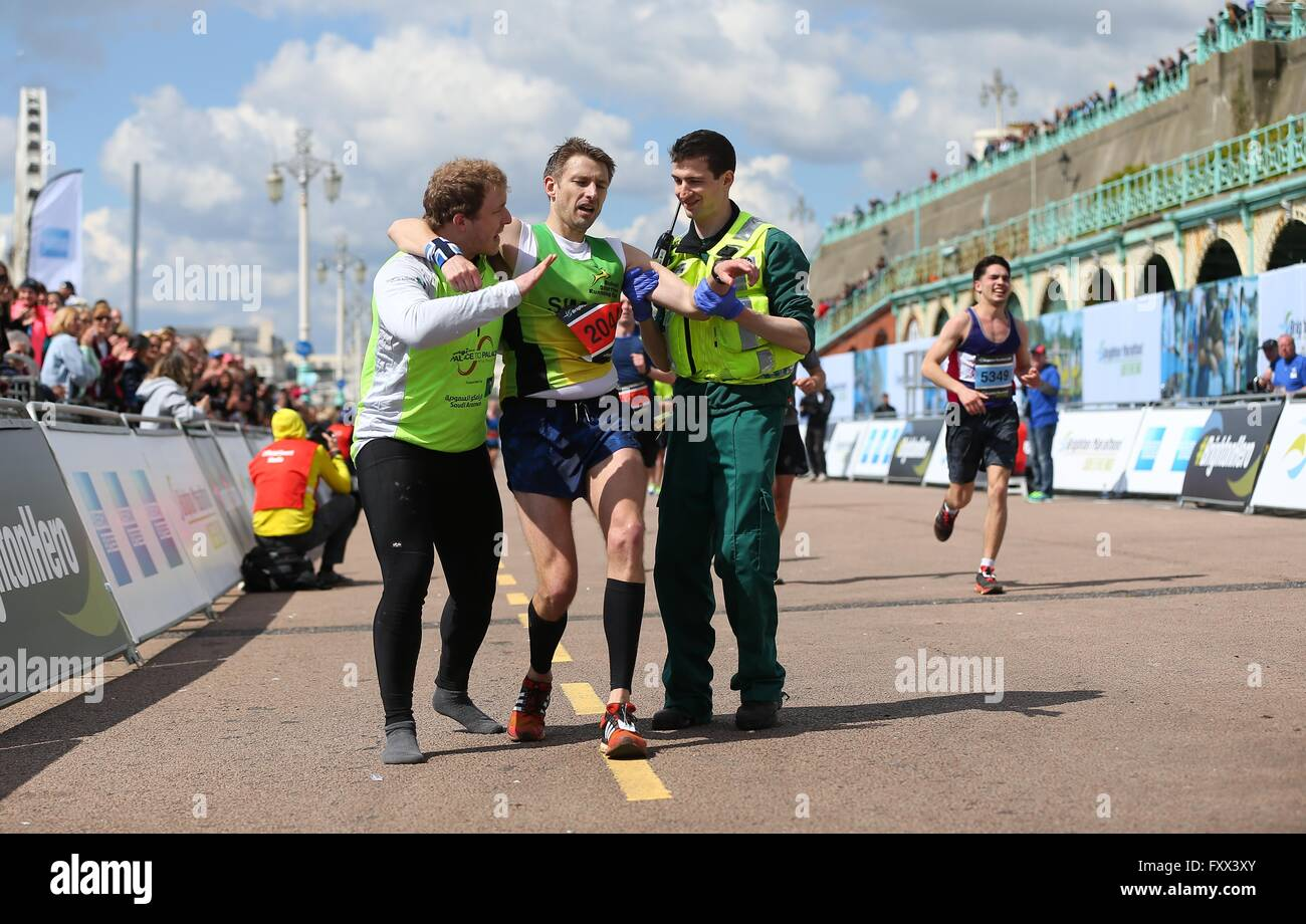 A paramedic and official helps a exhausted runner reach ...
