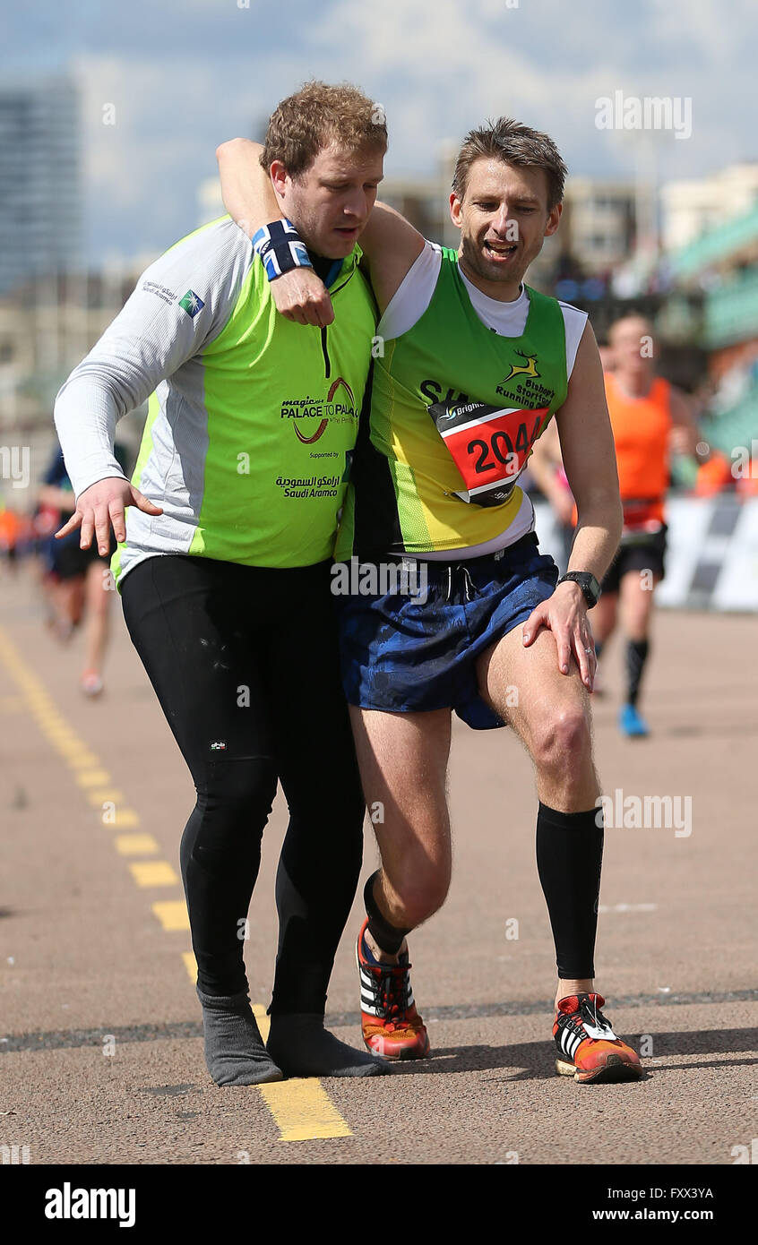 A Official helps an exhausted runner reach the finish line ...