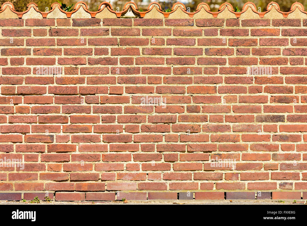 Red Brick Wall With A Row Of Roof Tiles On Top Stock Photo