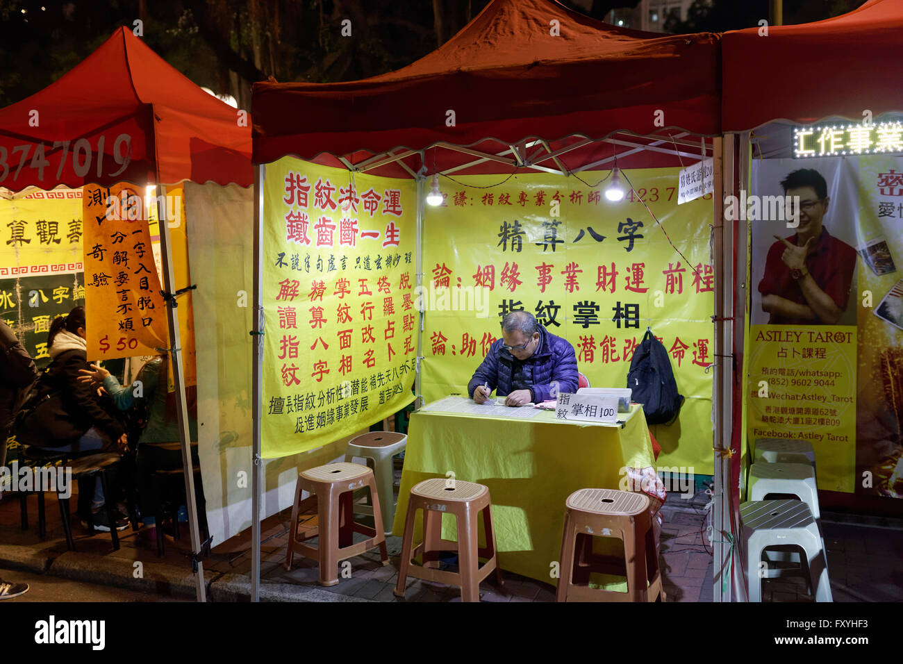 Chinese fortune tellers and palm readers in a lit tent Temple Street Night Market Yau Ma Tei Kowloon Hong Kong China & Chinese fortune tellers and palm readers in a lit tent Temple ...