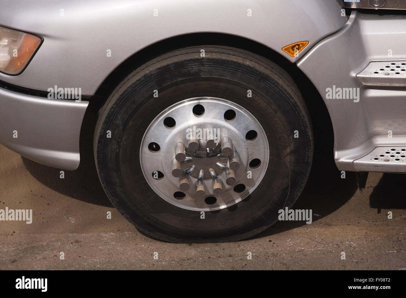 front left wheel and tire of a tractor trailer articulated lorry with a cracked aluminum hub