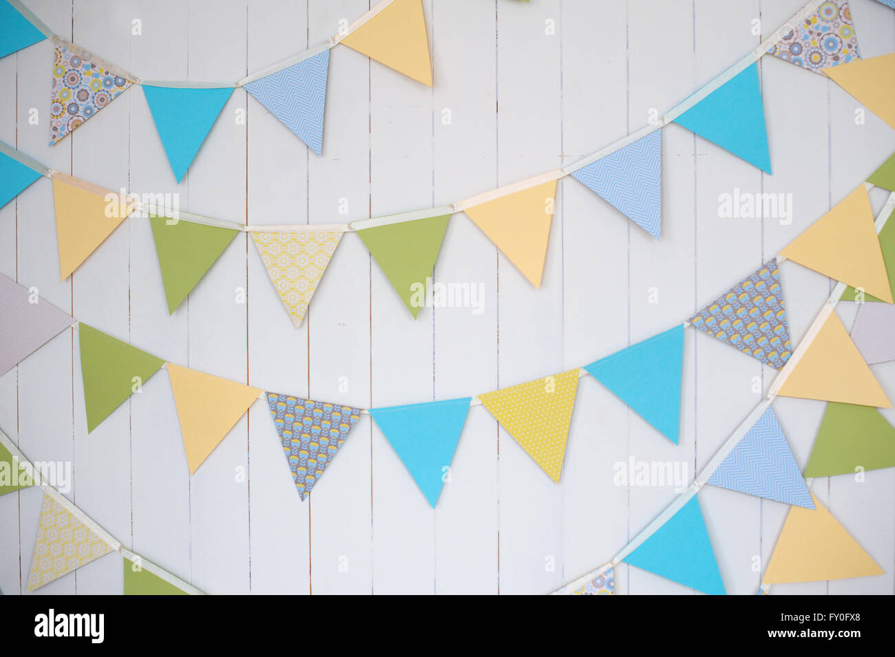 Birthday decoration flags on a plain white wall shot with tilt and