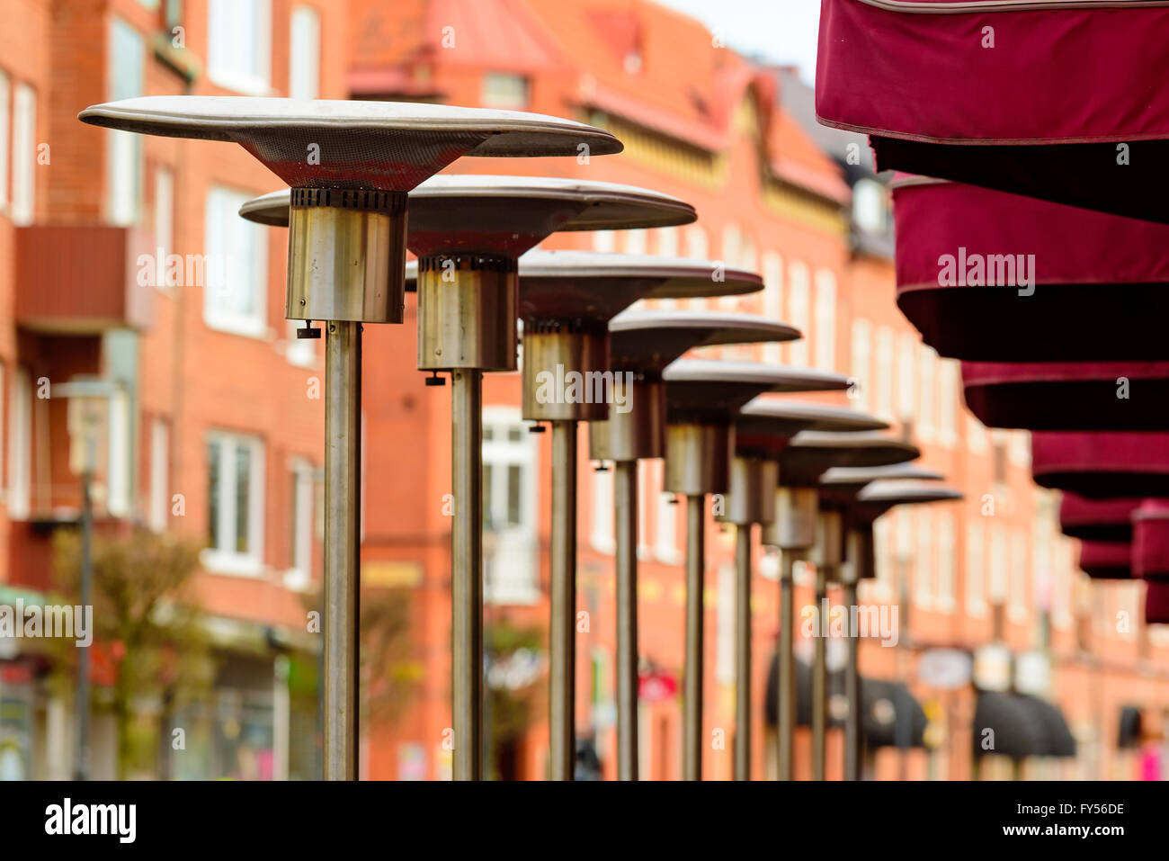 Delightful Row Of Patio Heaters Outside A Restaurant With City In Background. Also  Called Mushroom Heaters Or Umbrella Heaters.