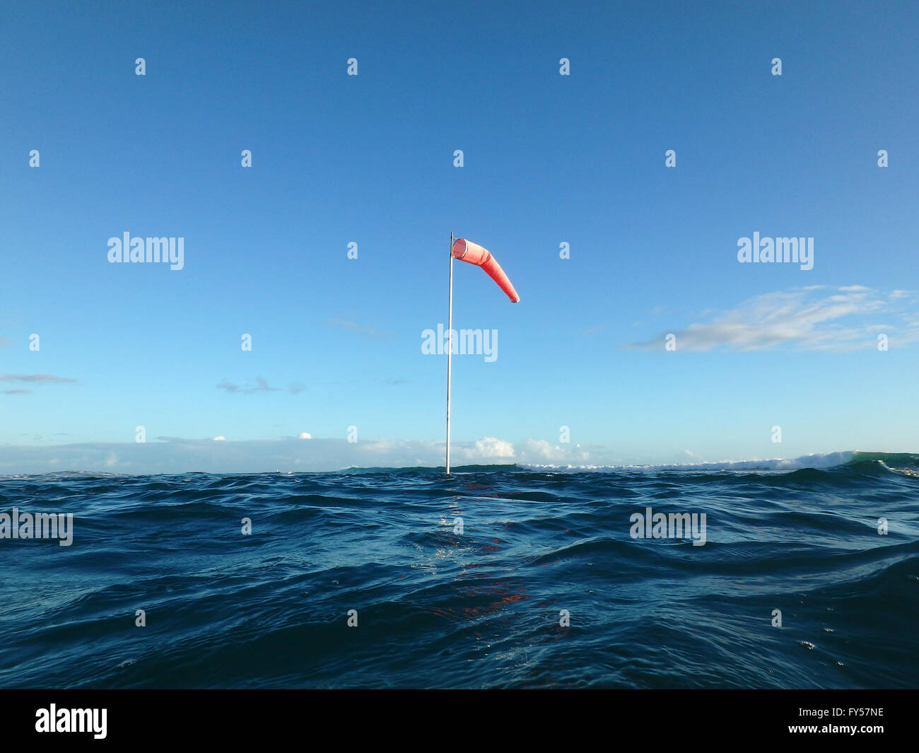 Flag pole with wind sock rises above the wavy waters of waikiki flag pole with wind sock rises above the wavy waters of waikiki hawaii sciox Image collections