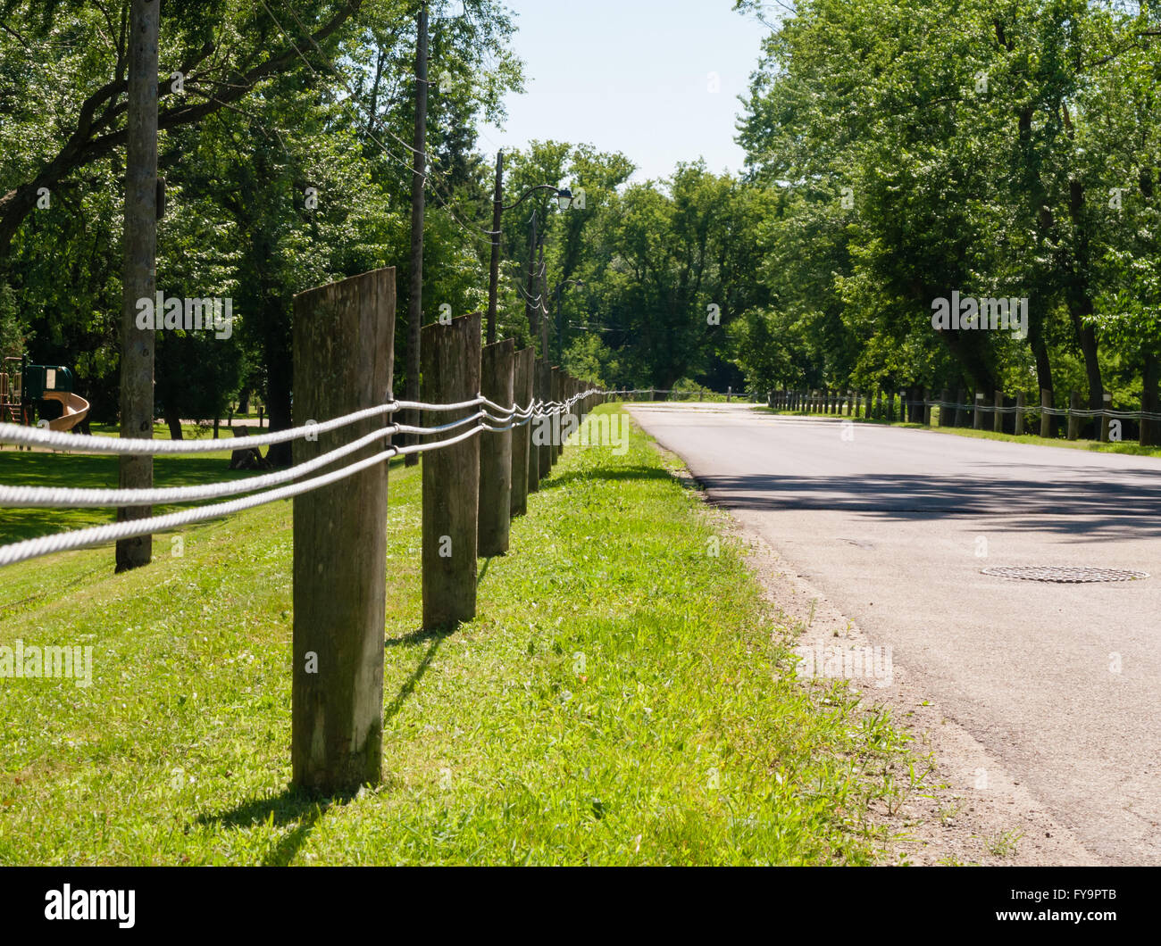 short wooden fence posts with three parallel steel lines along empty street in rural area in