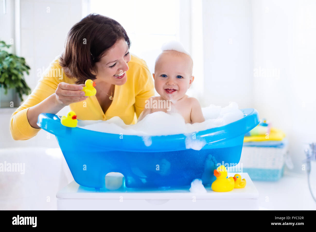 Happy baby taking a bath playing with foam bubbles. Mother washing ...