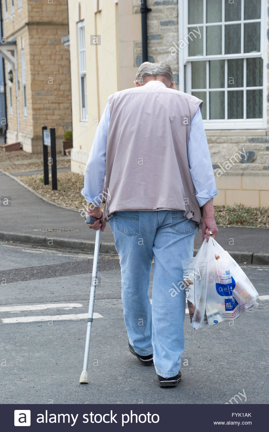 Elderly man crossing the road carrying bags of shopping in