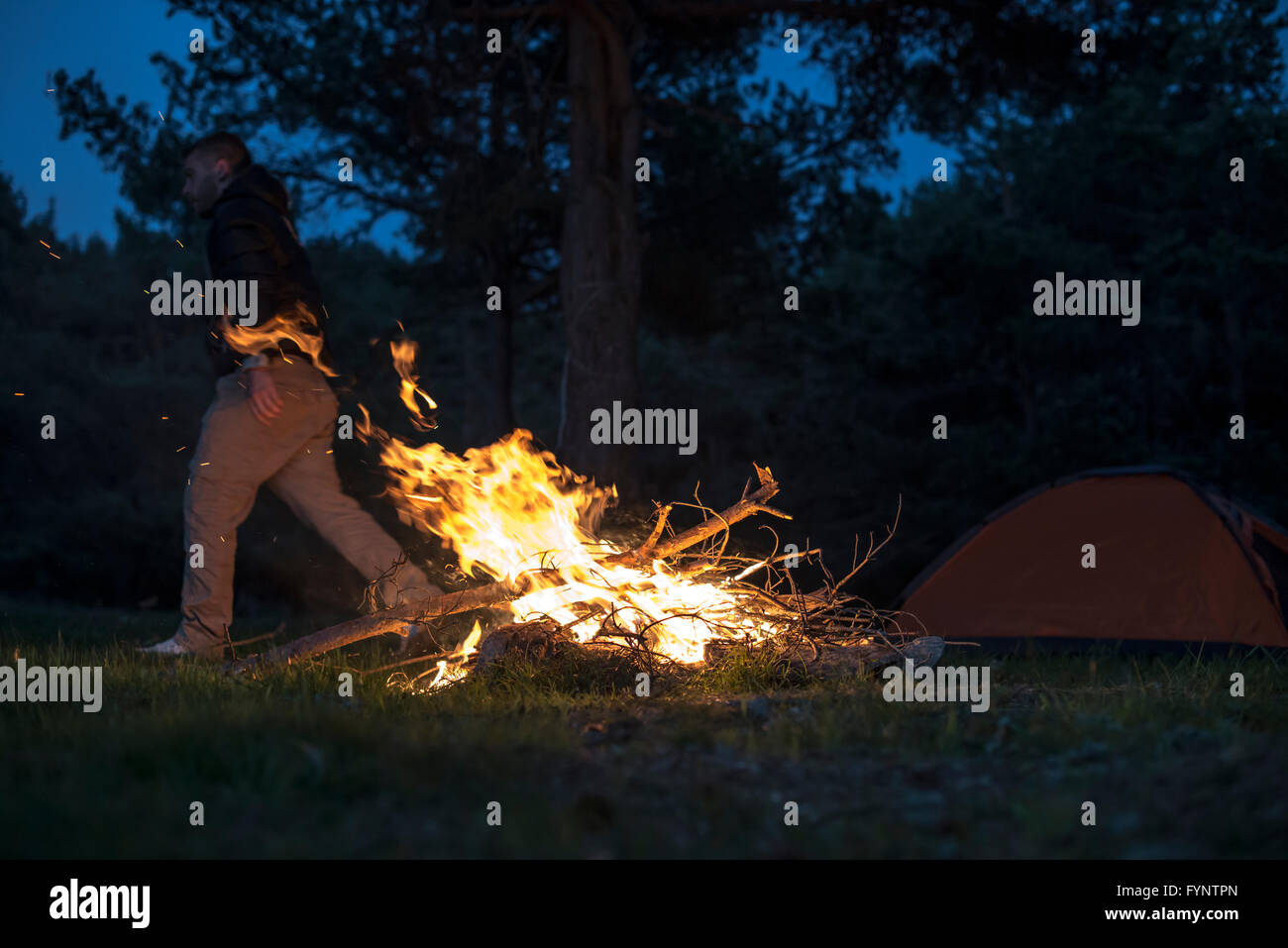 man lights a fire in the fireplace in nature at night stock photo