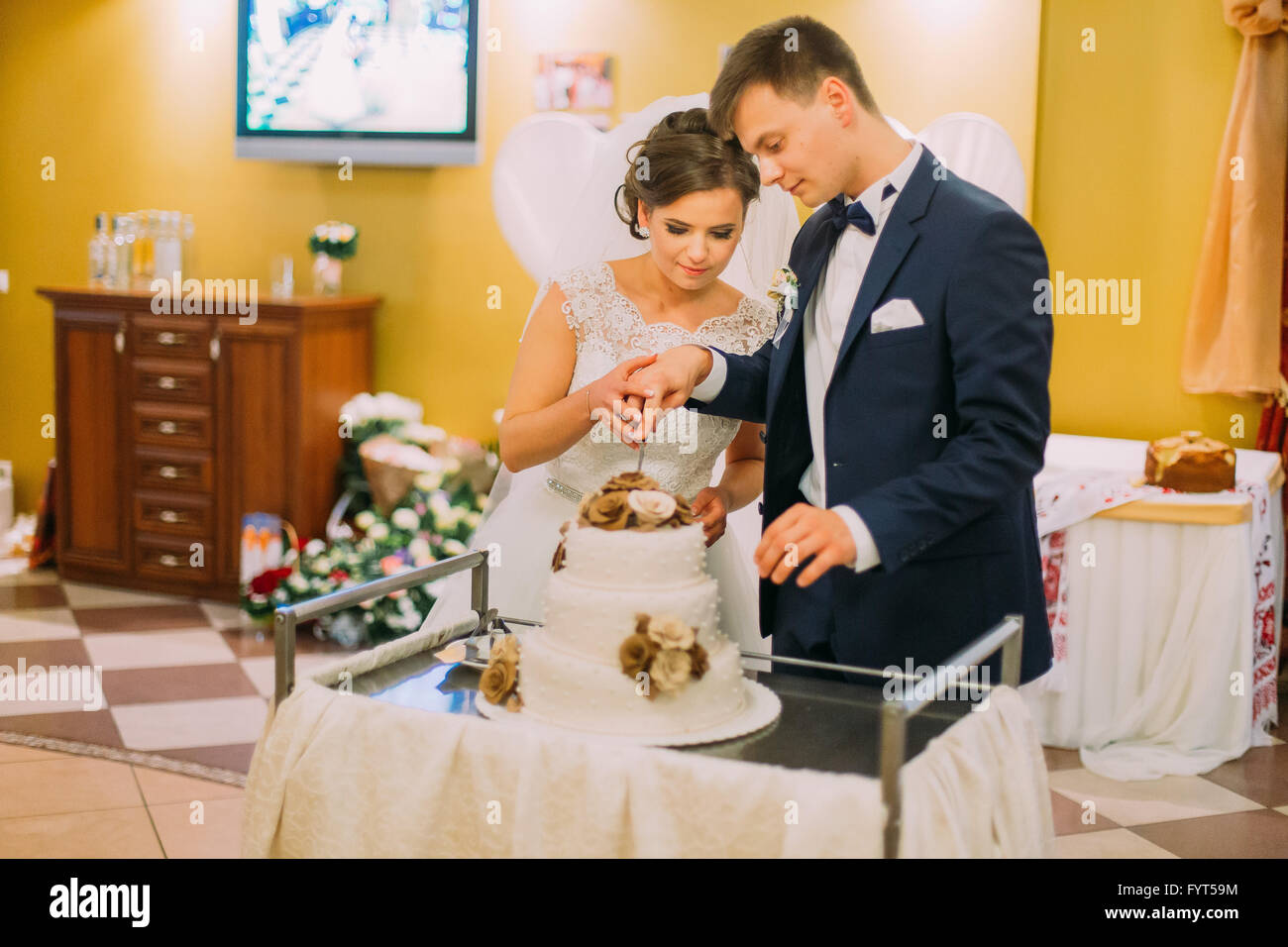 beautiful married couple cut the wedding cake decorated with beige