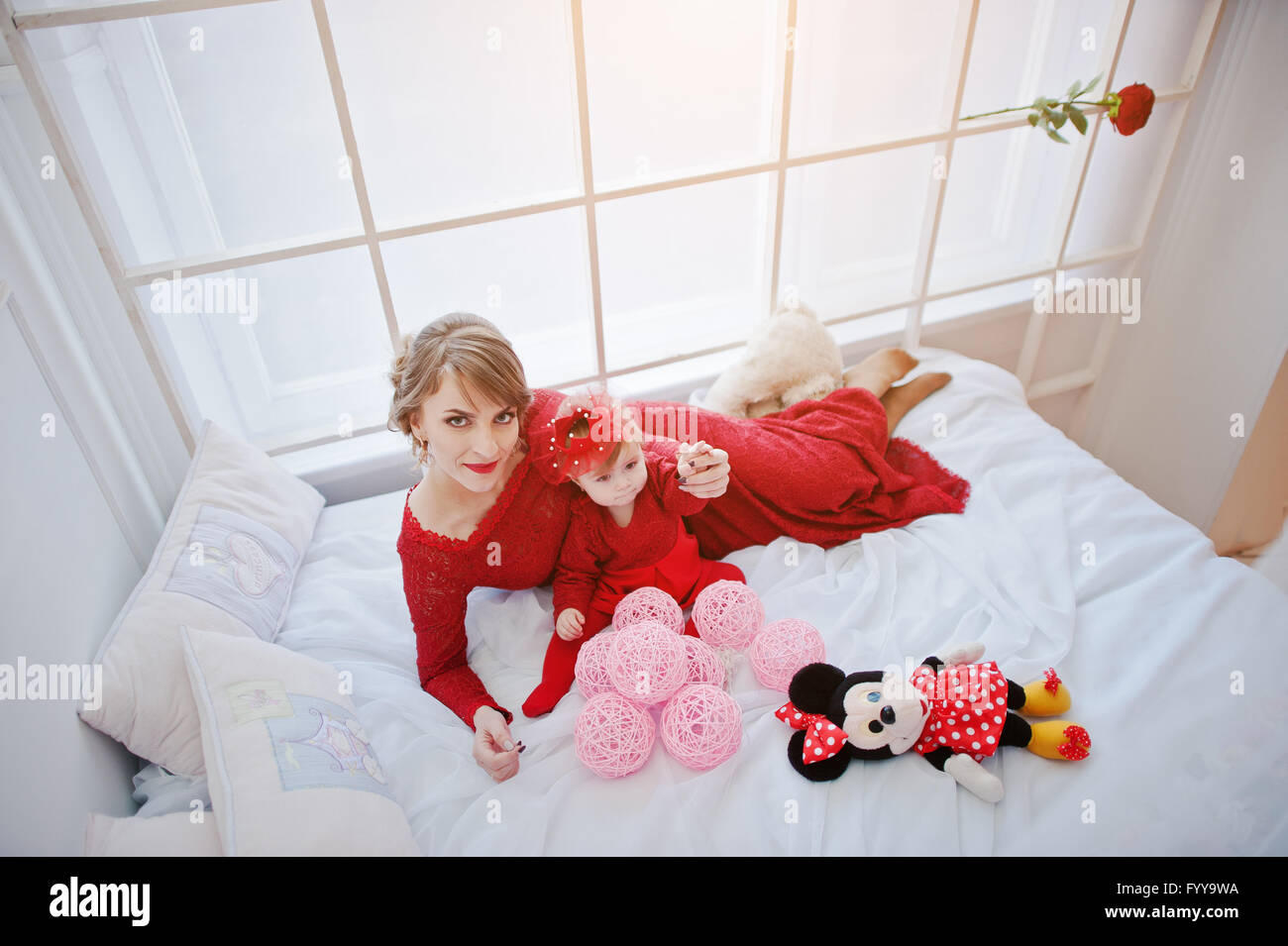 Mom with daughter in red dress lying on a big white bed Stock ...