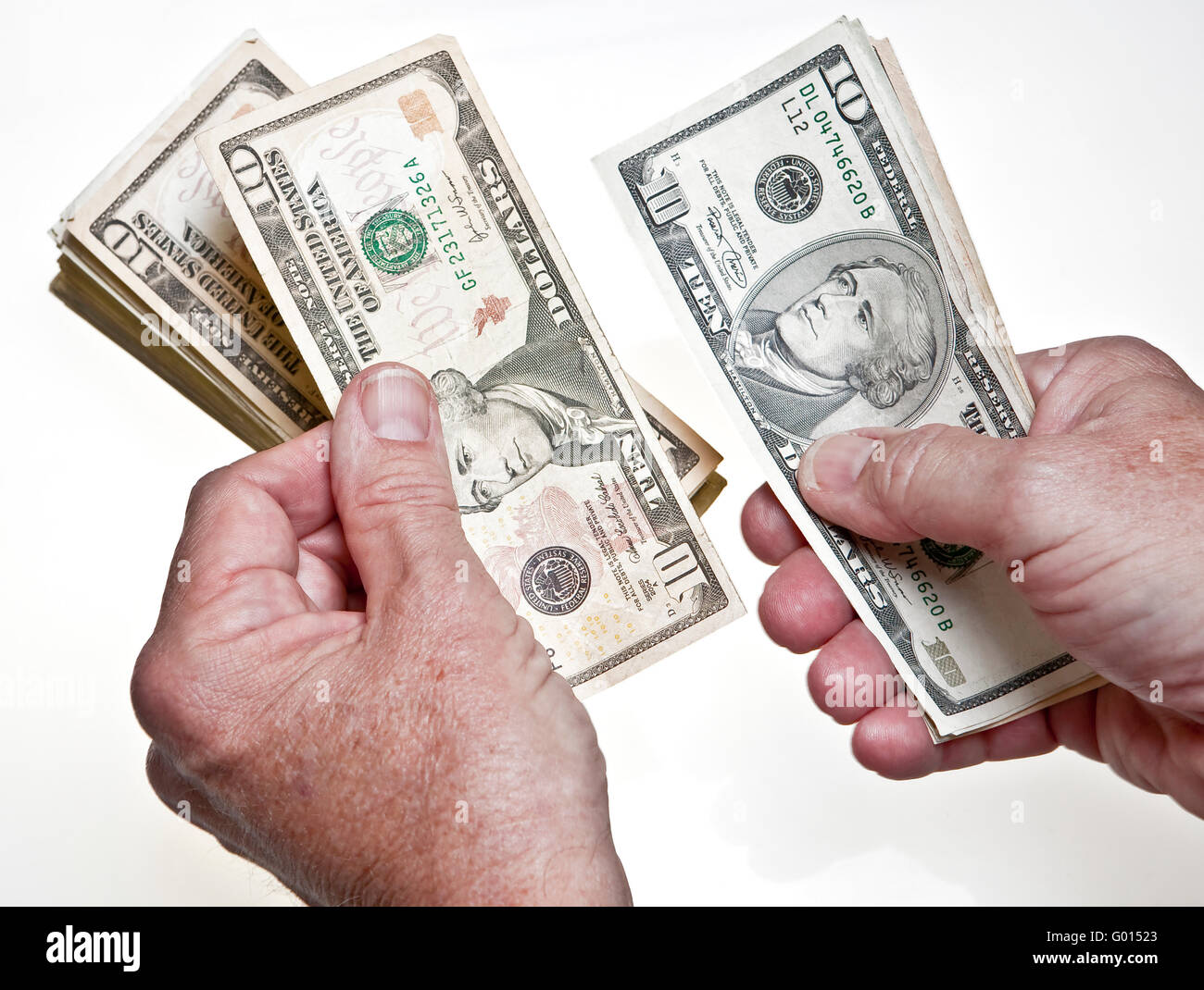 worksheet Counting Dollar Bills older mans hands counting ten dollar bills onto a stack on white background