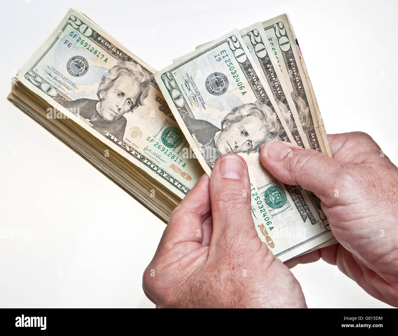 worksheet Counting Dollar Bills older mans hands counting twenty dollar bills onto a stack on white background