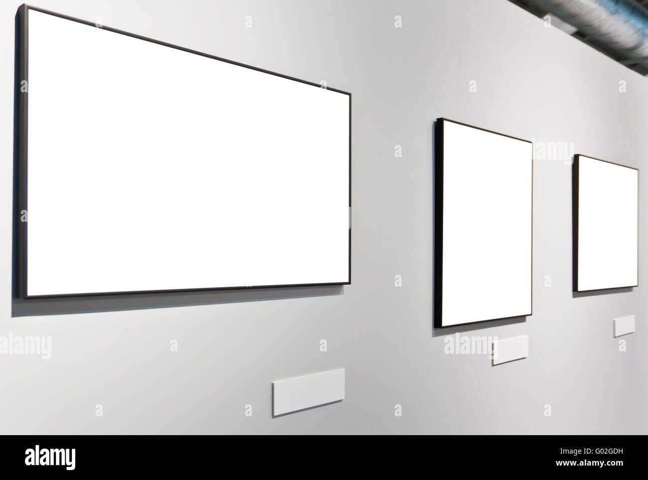 White wall in museum with three empty frames stock photo royalty white wall in museum with three empty frames sciox Images