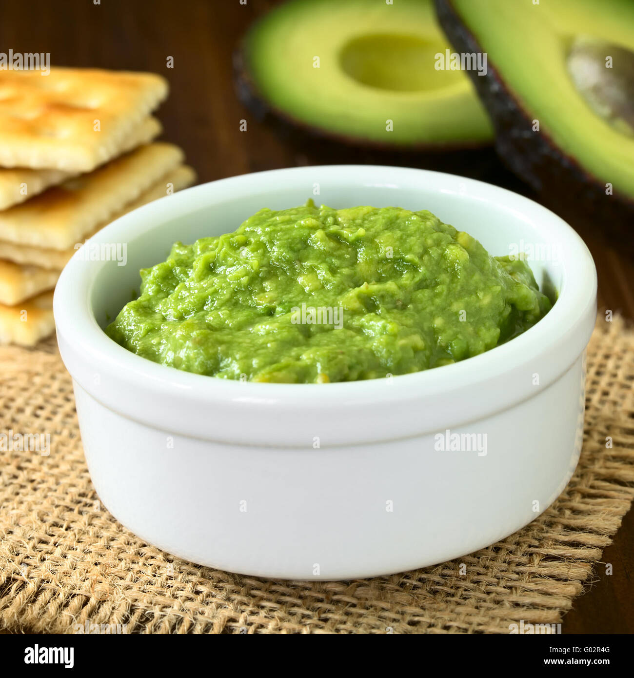 Fresh avocado cream or guacamole with soda crackers and ...