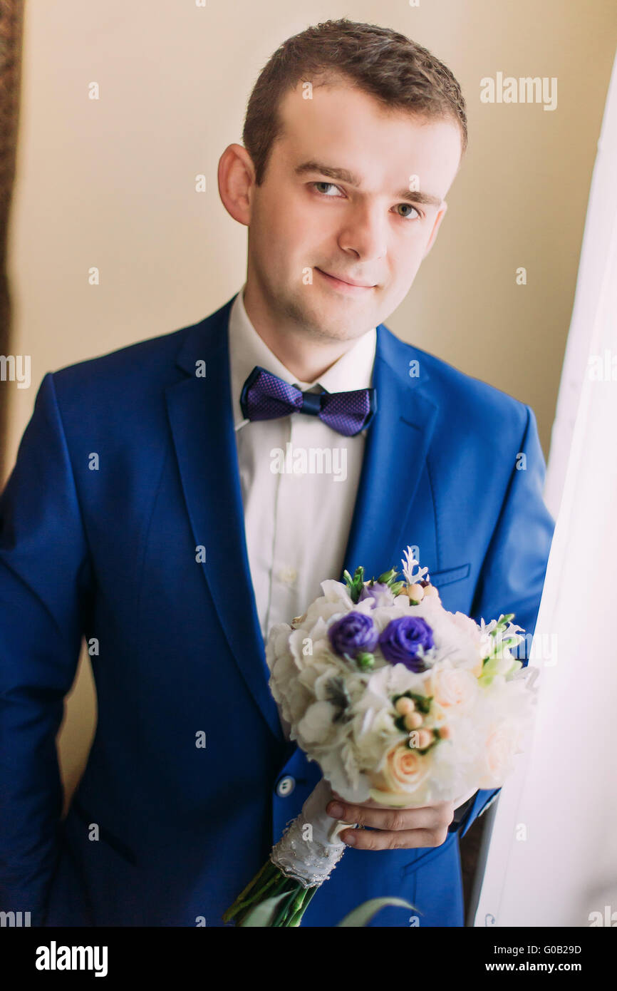 Cute stylish groom in blue suit and bow tie with a bouquet of ...