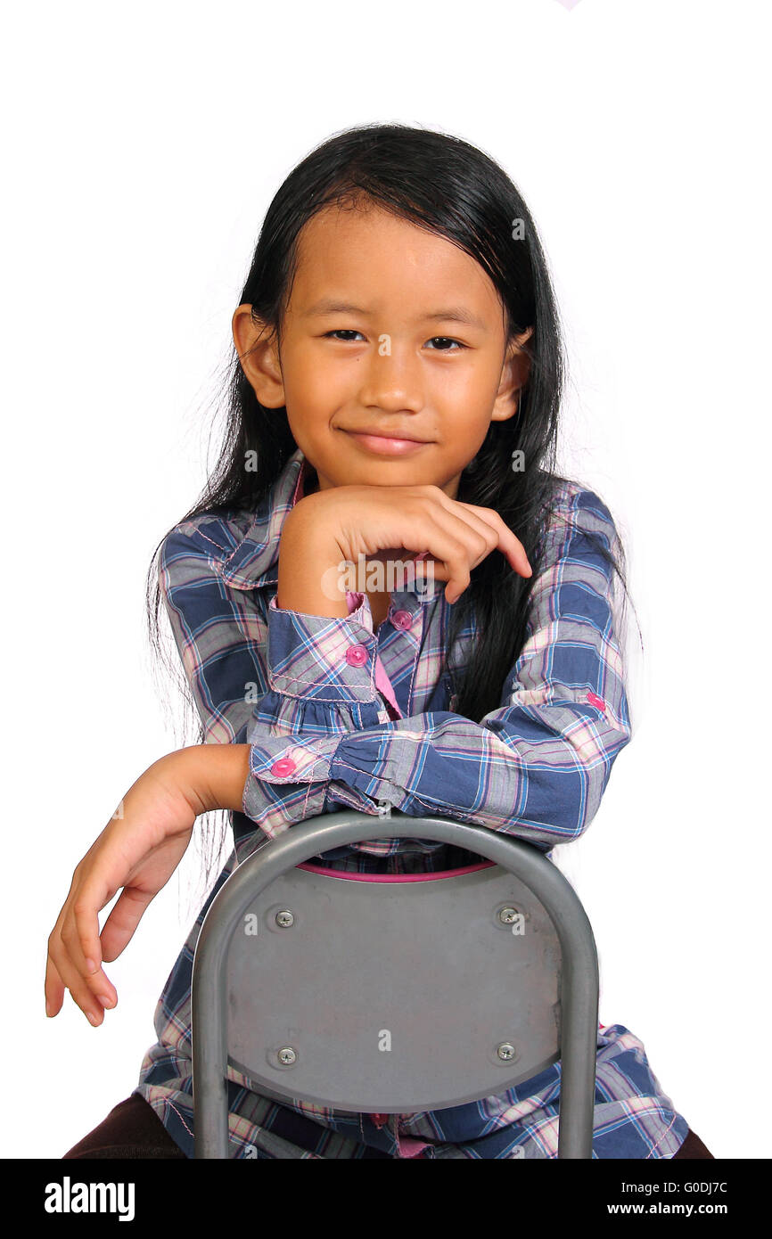Black child sitting in chair - Cute Little Girl Sitting Backward On Chair Smiling With Her Hand Under Chin Isolated On White